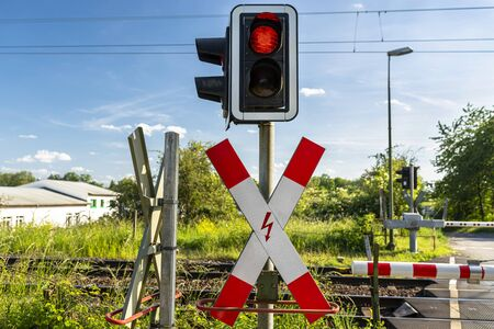 Guarded railroad crossing with closed barriers, red warning light and cross of Saint Andrew.