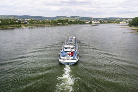 A large tanker ship sailing in Germany on the Rhine River. Transportation of oil, gas and gasoline, view from above.