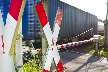 Closed barrier at the railroad crossing with St. Andrew cross, visible blurred blue wagon in motion. Stock Photo