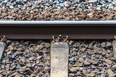 Railroad tracks lying on concrete sleepers, filling between large pieces of rock, close-up on the fastening screw.