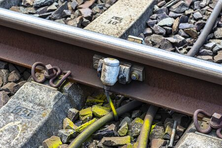 Railroad tracks lying on concrete sleepers, filling large pieces of rock, close-up on the axle counter detection unit.