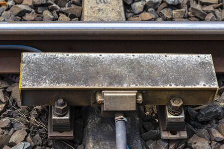 Automatic train braking system mounted on railway tracks, visible concrete sleepers and large stones between them. Banque d'images