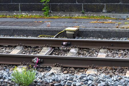Railroad tracks lying on concrete sleepers, filling large pieces of rock, visible system on the axle counter detection unit and pavement.