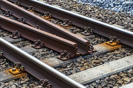 Railroad tracks lying on concrete sleepers, filling between large pieces of rock, spare tracks in the middle of the railway traction. Stock fotó
