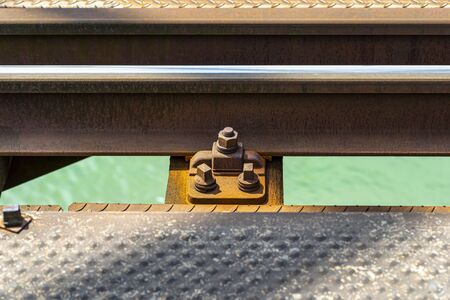 Railroad tracks located on the railroad bridge over the river, close-up on the fastening screw, lying on wooden sleepers, a turquoise river flows under the tracks.