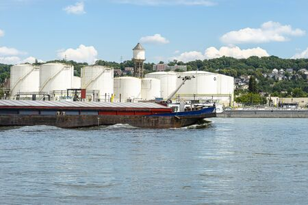 Storage silos, fuel depot of petroleum and gasoline on the banks of the river in western Germany on a beautiful blue sky with clouds. Visible coal barge. 版權商用圖片