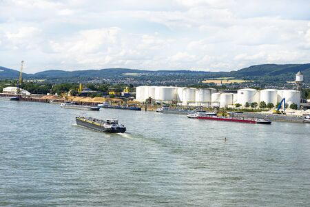 A large tanker ship sailing in Germany on the Rhine river visible storage silos, fuel depot of petroleum and gasoline on the banks river, loading port, heavy sea traffic.