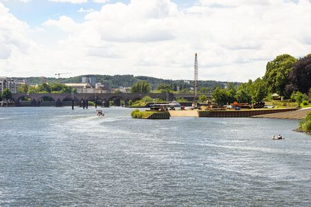 The Moselle River in the city center in West Germany, visible old concrete bridge and port for launching water units.