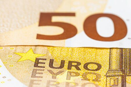 Macro shot of a European Union banknote of 50 EUR, close-up of the inscription EURO, selective focus.