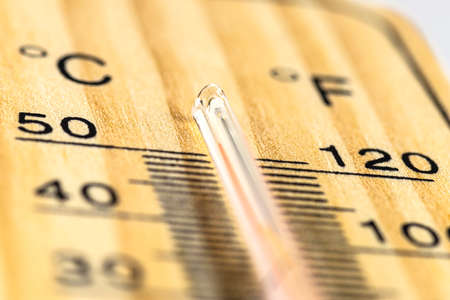 A macro shot of a classic wooden thermometer showing a temperature over 50 degrees Celsius, 122 degrees Fahrenheit.