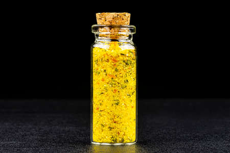 Macro shot of spice from salt and dried vegetables in a small glass bottle closed with a cork, isolated on a black background.