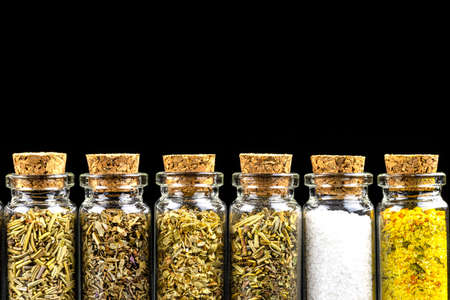 Macro shot of six different spices standing in a vials with a cork, isolated on a black background with space for text at the top.