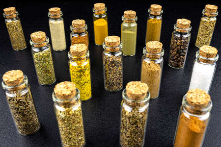 Macro shot of seventeen different spices standing in vials with a cork, isolated on a black background.