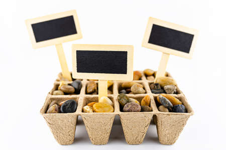 Three, wooden blank boards, label with stick, stuck in a cardboard extruder filled with decorative pebbles, conceptual photo, space for text, isolated on a white background. 写真素材