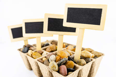 Four, wooden blank boards, label with stick, stuck in a cardboard extruder filled with decorative pebbles, conceptual photo, space for text, isolated on a white background.