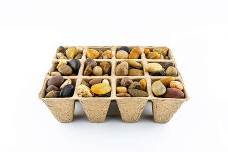 Cardboard extruder filled with colorful decorative pebbles, conceptual photo, space for text, isolated on a white background.