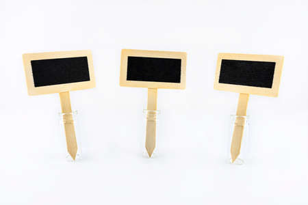 Three empty wooden signs with a black center on a stick stuck in a glass vial, isolated on a white background.