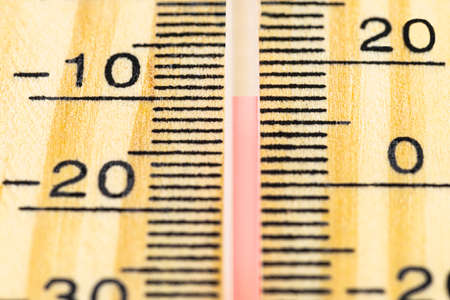 A macro shot of a classic wooden thermometer showing a temperature -10 degrees Celsius, 14 degrees Fahrenheit. 写真素材