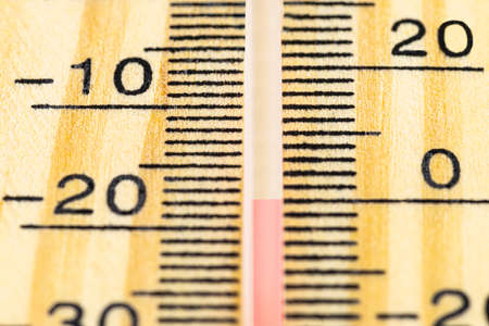 A macro shot of a classic wooden thermometer showing a temperature -17.7 degrees Celsius, 0 degrees Fahrenheit.