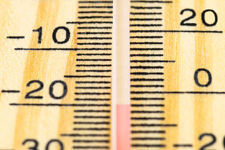 A macro shot of a classic wooden thermometer showing a temperature -20 degrees Celsius, -4 degrees Fahrenheit.