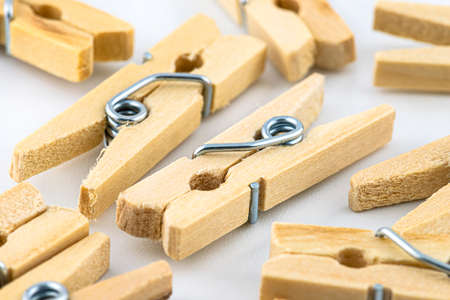 Macro shot of miniature, wooden clamps lying in a group on a white background. 写真素材