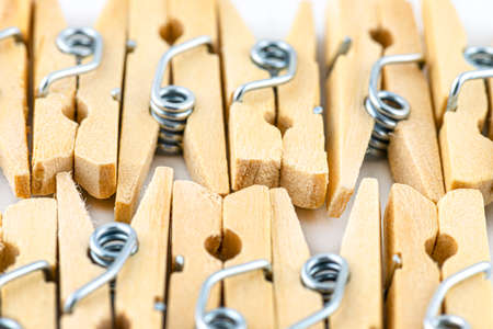 Macro shot of miniature, wooden clamps lying in two rows on a white background.