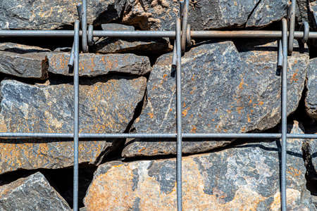Background made of a stone wall secured with a galvanized metal mesh, close-up shot. 写真素材