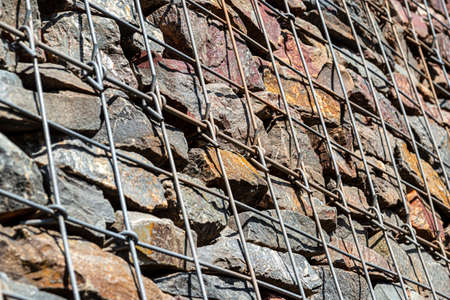 Background made of a stone wall secured with a galvanized metal mesh. 写真素材
