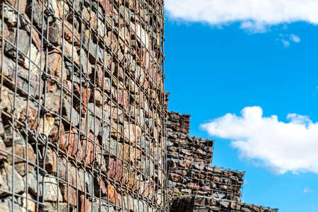 A stone wall standing by the road, made of stones protected by metal, galvanized mesh in the background of the blue sky with clouds, selective focus.