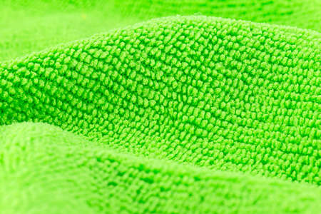 Background made of green microfiber fabric, selective focus.