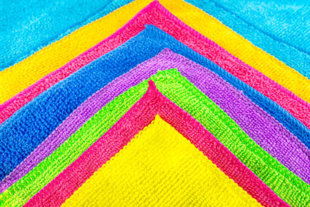 Background made of different colors of microfiber material superimposed on each other, in the shape of a triangle.