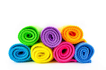 Background made of different colors of microfiber material, rolled up and stacked on top of each other, front view.