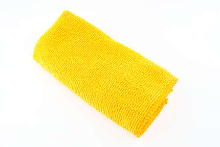 Orange microfiber fabric lying in the middle, isolated on a white background, top view.