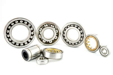 Background made of several ball bearings, isolated on a white background, selective focus, in the background the bearings standing in a row.