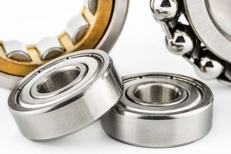 Macro shot of two ball bearings, isolated on a white background, selective focus.