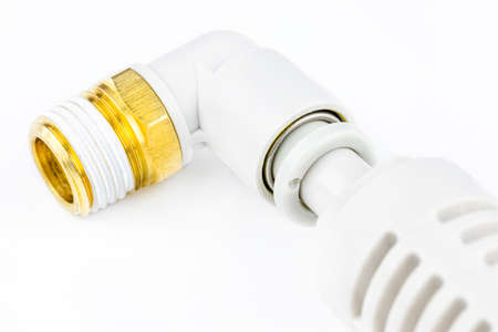 Macro shoot of a white pneumatic air silencer for pneumatic installations connected with pneumatic elbow for plastic pipe with brass external thread, isolated on a white background. 写真素材