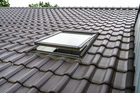 One open roof window in the attic, visible anthracite ceramic tiles.