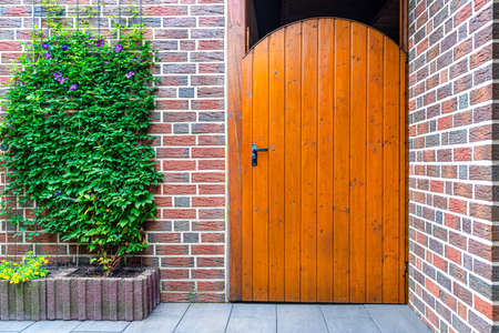 Closed wooden garden door with key inside with black handle, visible red brick wall.