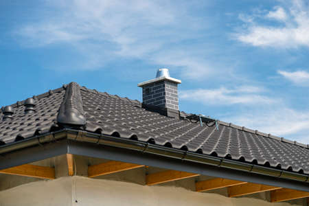 The roof of a single-family house covered with a new ceramic tile in anthracite against the blue sky, visible ridge tile, system chimney and ceramic ventilation fireplace on the roof.