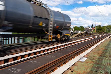 Blurry photo of railroad tank cars in motion, on a metal bridge over the river. 写真素材