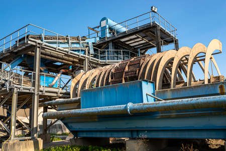 Cement mill sand dewatering machine and machine for transferring gravel, spoil for transport belts on blue sky at an industrial cement plant. Stock fotó