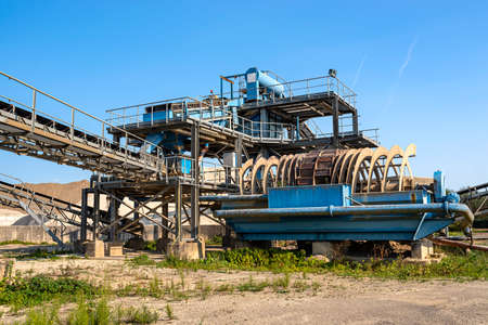 Cement mill sand dewatering machine and machine for transferring gravel, spoil for transport belts on blue sky at an industrial cement plant. Stock fotó - 155368312