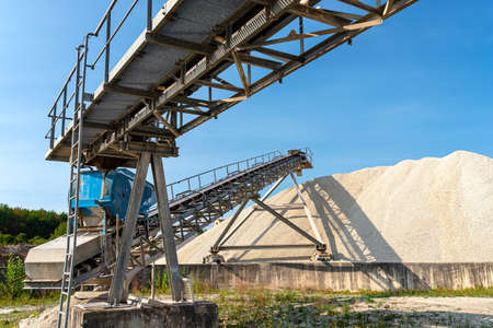 A system of interconnected conveyor belts over heaps of gravel against a blue sky at an industrial cement plant. Stock fotó - 155372881
