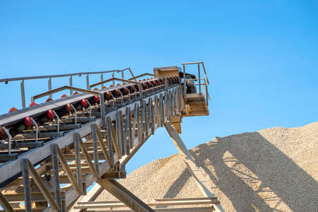 Conveyor belt over heaps of gravel against the blue sky at an industrial cement plant. Stock fotó - 155372616