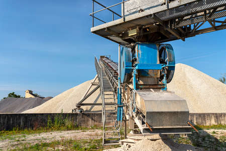 A system of interconnected conveyor belts over heaps of gravel against a blue sky at an industrial cement plant. Stock fotó - 155373039