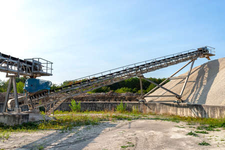 A system of interconnected conveyor belts over heaps of gravel against a blue sky at an industrial cement plant.
