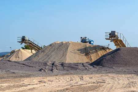 Conveyor belt over heaps of gravel against the blue sky at an industrial cement plant.