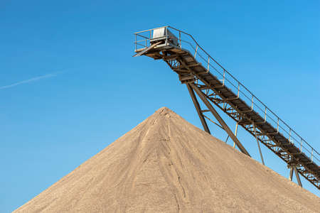 Conveyor belt over heaps of gravel against the blue sky at an industrial cement plant. Banque d'images