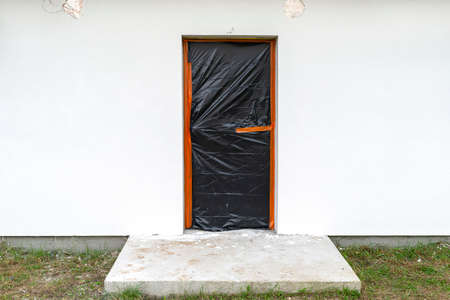 A newly applied layer of white silicone plaster on the wall of the house, the door is secured with black foil. Banco de Imagens