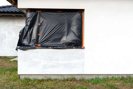 A newly applied layer of white silicone plaster on the wall of the house, the corner window is protected with black foil.